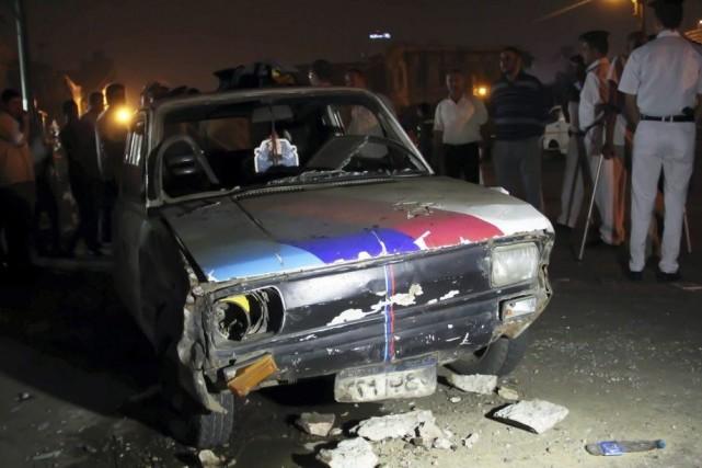 Des policiers inspectent une voiture endommagée par l'explosion... (PHOTO AL YOUM AL SAABI, REUTERS)