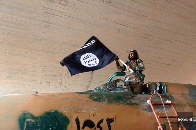 Un militant brandit le drapeau de l'EI en... (Photothèque Le Soleil)