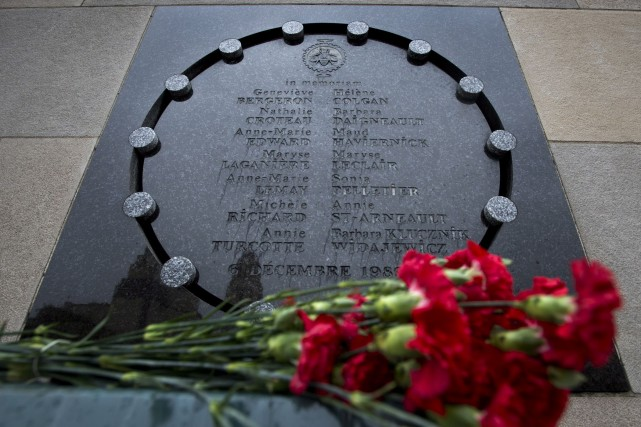 Des fleurs déposées près de la plaque rendant... (Photo archives La Presse Canadienne)