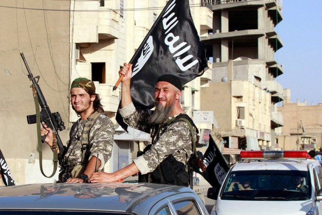 Des combattants du groupe État islamique paradent dans... (PHOTO ARCHIVES REUTERS)