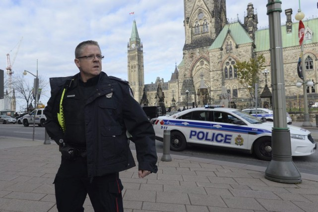 A police officer secures the scene of a... (Adrian Wyld, La Presse Canadienne)
