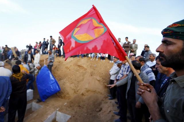 Un homme brandit un drapeau kurde lors des... (PHOTO KAI PFAFFENBACH, REUTERS)