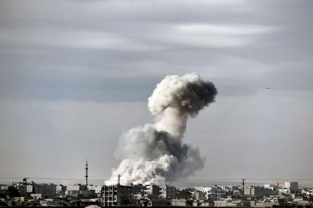 Une colonne de fumée s'élève de la ville... (PHOTO ARIS MESSINIS, ARCHIVES AFP)