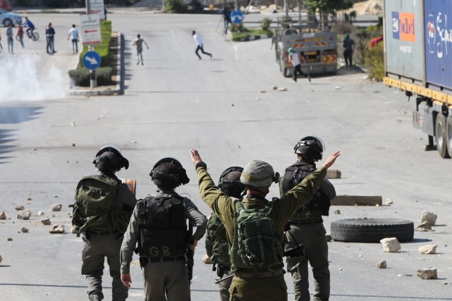Des soldats israéliens font face à des manifestants... (PHOTO HAZEM BADER, ARCHIVES AFP)