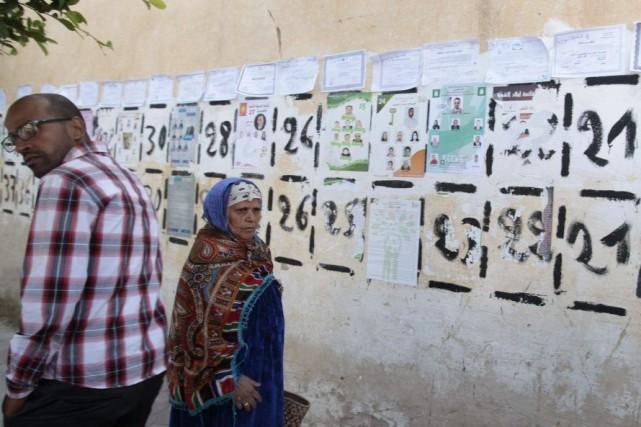 Des gens passent devant des affiches électorales posées... (PHOTO ZOUBEIR SOUISSI, REUTERS)