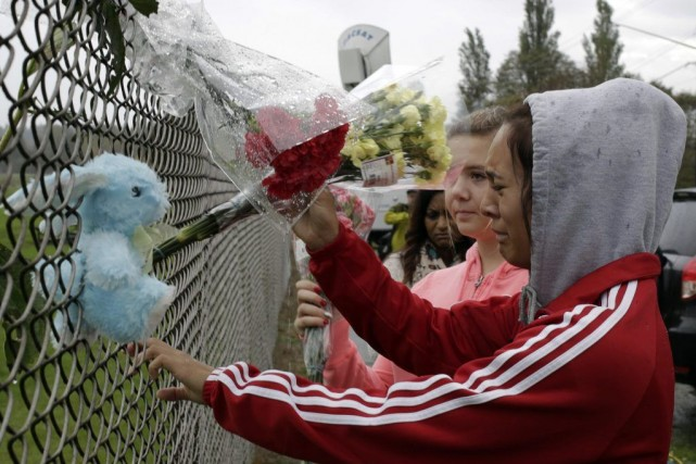Des élèves déposent des fleurs sur la clôture... (PHOTO JASON REDMOND, REUTERS)
