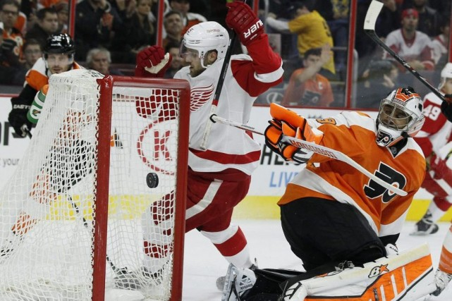 Riley Sheahan des Red Wings réussit à déjouer la... (Photo Tom Mihalek, AP)