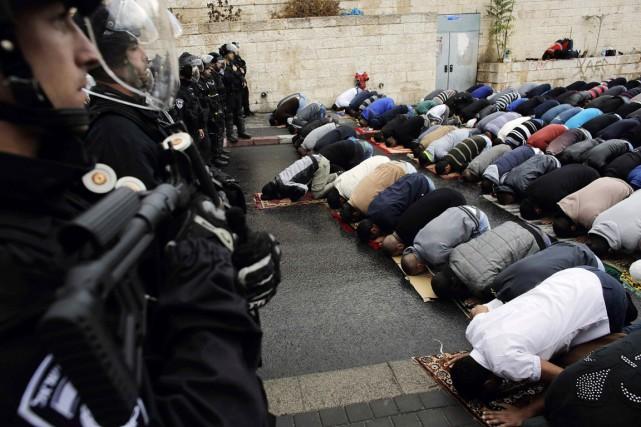 Des Palestiniens prient devant des policiers anti-émeutes israéliens... (PHOTO AMMAR AWAD, REUTERS)