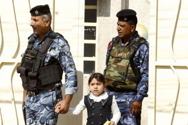 Des policiers irakiens, qui accompagnent ici une petite... (Photo Reuters)