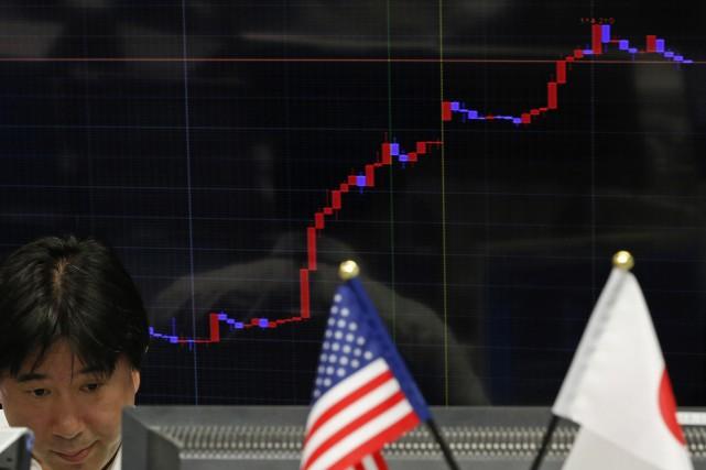 Le dollar est repassé brièvement jeudi vers 11h00 à Tokyo (22h00, mercredi,... (Photo YUYA SHINO, Reuters)