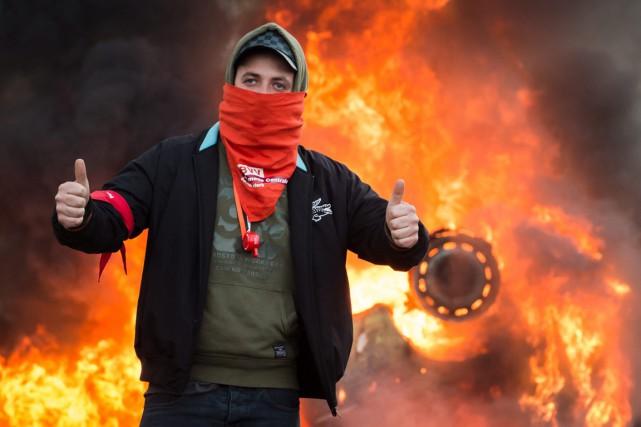 Un manifestant prend la pose devant une voiture... (PHOTO GEERT VANDEN WIJNGAERT, AP)