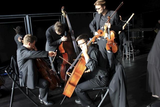 Les basses accordent leurs instruments avec un concert,... (Photo Michelle Seto)