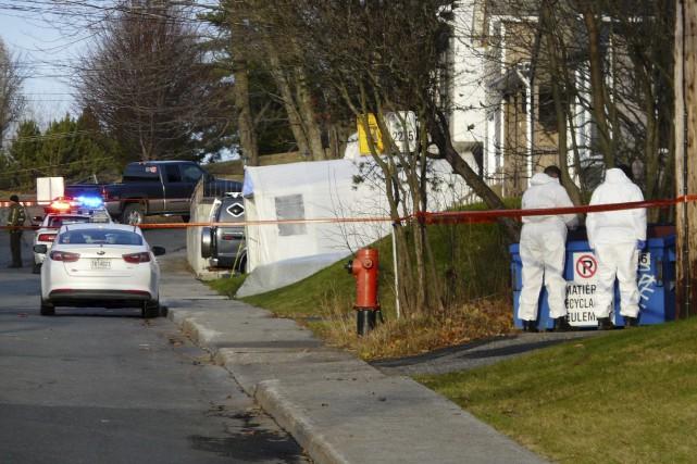Les criminalistes passent les poubelles de la 123e... (Collaboration spéciale Luce Dallaire)