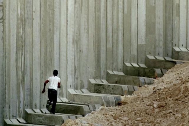 Un Palestinien devant l'impressionnant mur entre Israël et... (Archives REUTERS/Reinhard Krause)
