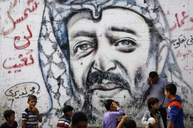 Des garçons palestiniens jouent à proximité d'un graffiti... (PHOTO MOHAMMED ABED, ARCHIVES AFP)