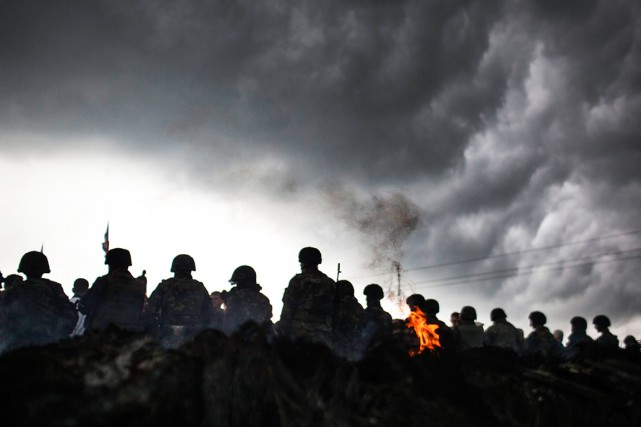 Des soldats ukrainiens font face à des civils... (PHOTO MANU BRABO, ARCHIVES AP)