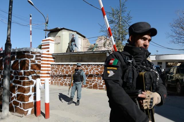 Des policiers montent la garde devant le QG... (PHOTO SHAH MARAI, ARCHIVES AFP)