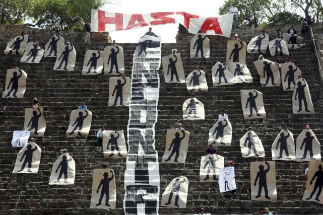 Des manifestants ont déployé des bannières représentant les... (PHOTO JORGE LUIS PLATA, REUTERS)