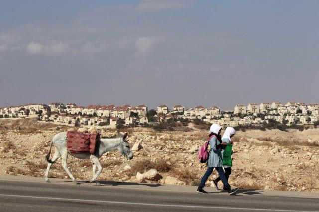 Des écolières tirent un âne sur une route... (PHOTO AMMAR AWAD, REUTERS)