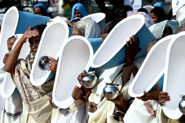 Des femmes portent des latrines alors qu'elles participent... (PHOTO ROBERTO SCHMIDT, AFP)