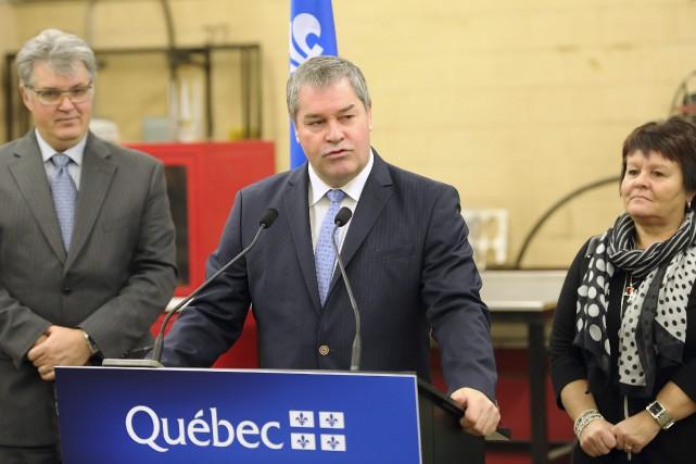 Le ministre Yves Bolduc, entouré du directeur du... ((Photo Gimmy Desbiens))