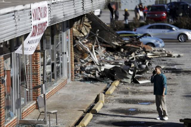 Un propriétaire de restaurant regarde les dommages causés... (Associated Press)