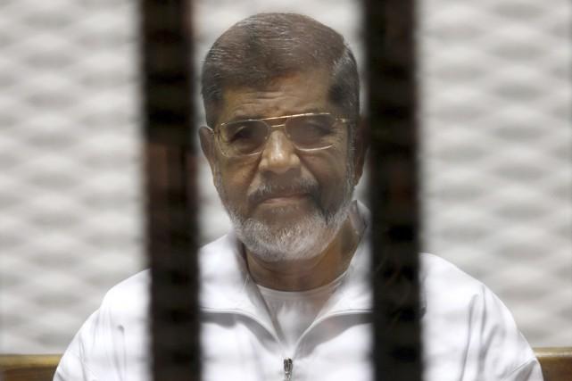 Le président déchu Mohamed Morsi est vu derrière... (PHOTO ARCHIVES REUTERS/STRINGER)