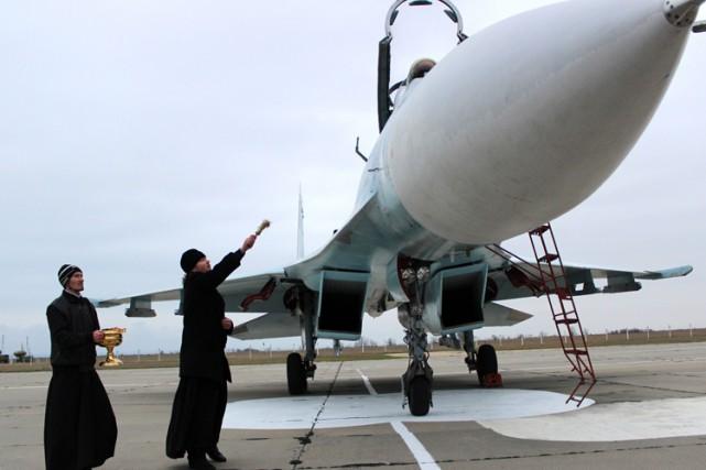 Un prêtre orthodoxe bénit unavion de chasse russe... (Photo: AFP)