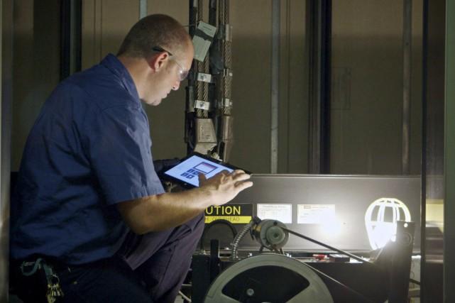 Un technicien observe un ascenseur équipé de capteurs... (Photo Microsoft)