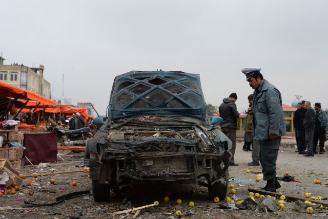 Un policier examine une voiture ayant explosé àMazâr-e... (PHOTO FARSHAD USYAN, AFP)