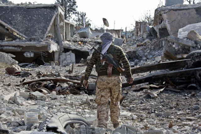 Un combattant kurde marche dans une rue de... (PHOTO JAKE SIMKIN, AP)