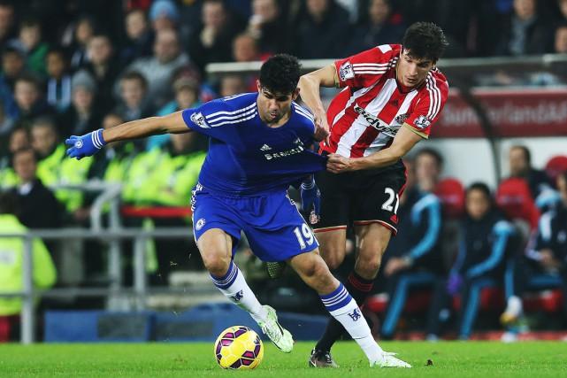 Diego Costa (19) tente d'échapper au défenseur Santiago... (PHOTO IAN MACNICOL, AFP)