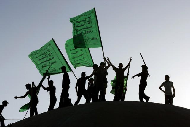 Des Palestiniens brandissent des drapeaux du Hamas, une... (PHOTO THOMAS COEX, ARCHIVES AGENCE FRANCE-PRESSE)