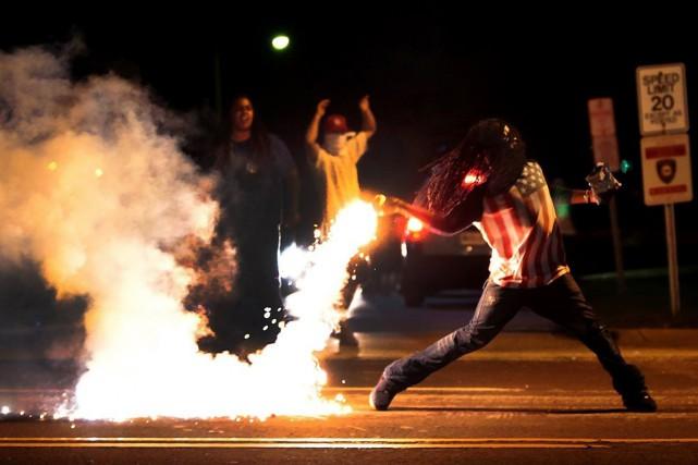 Un manifestant relance une bombe de gaz lacrymogène... (PHOTO ROBERT COHEN, MCT/BUZZFEED)