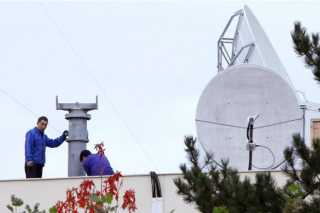 Trois antennes paraboliques qui, depuis la banlieue parisienne,... (PHOTO BRUNO COUTIER, L'OBS)