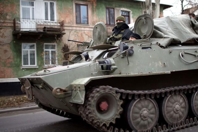 Des combattants prorusses patrouillent à bord d'un char... (PHOTO MENAHEM KAHANA, ARCHIVES AFP)