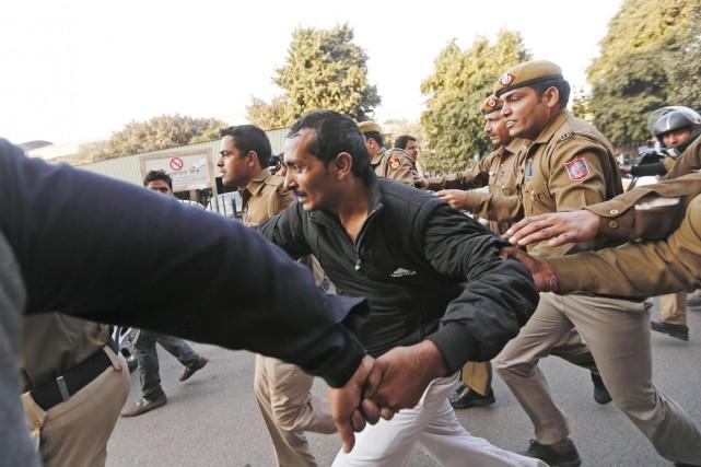 Des policiers escortent au pas de course le... (PHOTO ADNAN ABIDI, REUTERS)