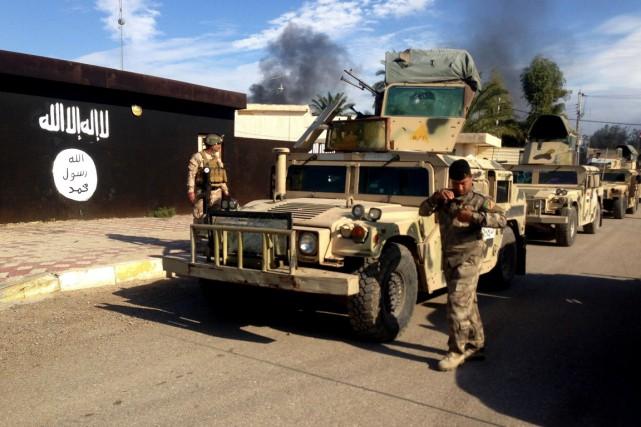 Des soldats irakiens sont déployés devant le «tribunal»... (PHOTO ARCHIVES AP)