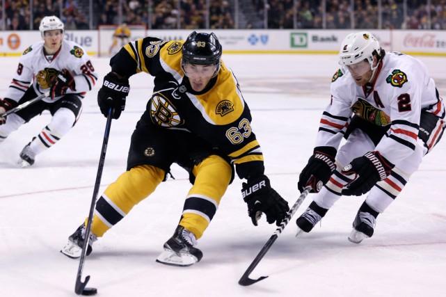 Brad Marchand, avec les Bruins, et Duncan Keith,... (Photo AP)