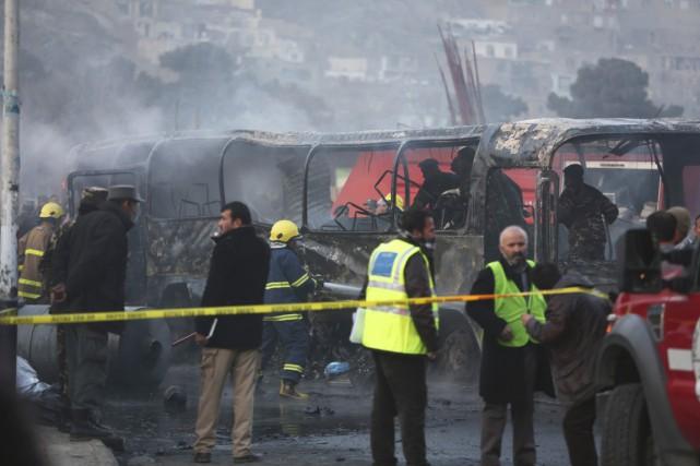 Des pompiers inspectent un autobus de l'armée nationalevisé... (PHOTO RAHMAT GUL, AP)