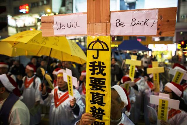 Un manifestant tient une croix où il est... (PHOTO ATHIT PERAWONGMETHA, REUTERS)