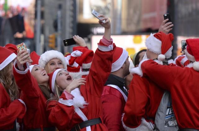 Des gens déguisés en Père Noël se prennent... (Agence France-Presse)