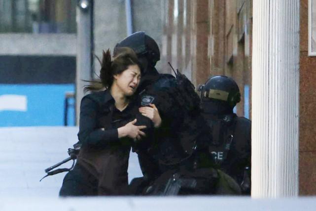 Une otage, tout juste sortie du café, se... (PHOTO JASONREED, REUTERS)