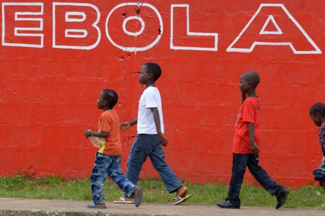 Des enfants passent devant une murale deMonrovia, au... (PHOTO DOMINIQUE FAGET, ARCHIVES AFP)