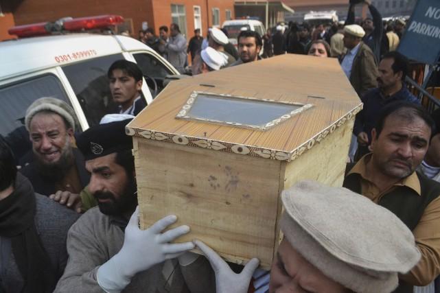 Les gens portent le cercueil d'une des 141victimes... (AP, Mohammad Sajjad)