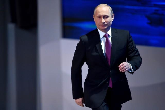 Vladimir Poutine arrive en scène pour sa conférence... (PHOTO ALEXANDER NEMENOV, AFP)