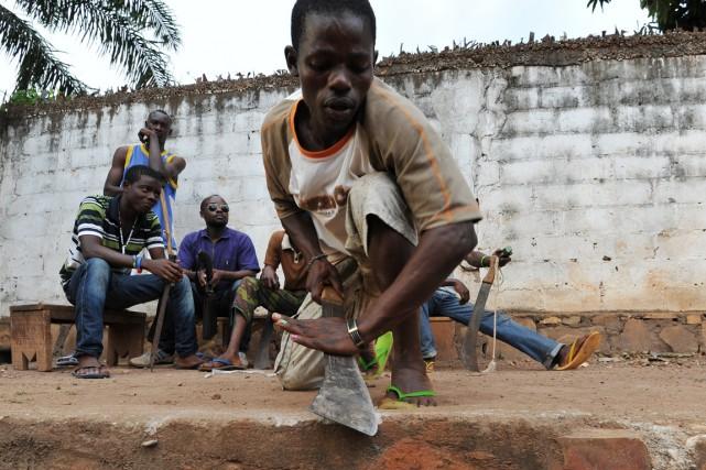 Un homme, faisant partie d'une milice d'autodéfense, aiguise... (PHOTO SIA KAMBOU, ARCHIVES AFP)