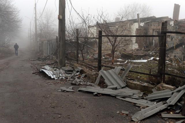 Un homme marche devant un maison endommagée par... (PHOTO VASILY MAXIMOV, AFP)