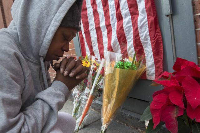 Des citoyens sont venus déposer bougies et fleurs... (Photo Stephanie Keith, Reuters)