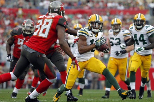 Randall Cobb (18) tente de contourner Dashon Goldson... (PHOTO KIM KLEMENT, USA TODAY)